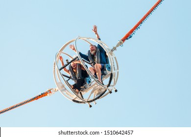 28 July 2019, Paris, France: Couple laughing and rejoicing at Catapult attraction at amusement Park