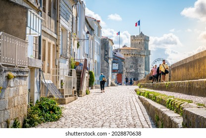 28 July 2021 , La Rochelle France : Beautiful view of the Chain and Saint Nicolas Towers and Sur-Les-Murs medieval street and tourists in La Rochelle historic center France