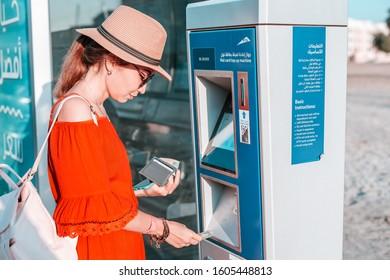 28 November 2019, UAE, Dubai: Tourist girl top up her Nol transport card in Atm terminal near bus stop