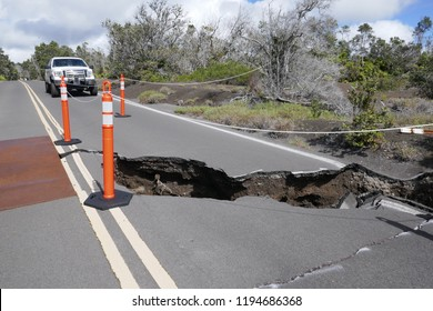 28 SEPTEMBER 2018, Volcano National Park, Hawai'i, USA - Ranger car parked by a road sinkhole, following earthquakes caused by eruption of Kīlauea volcano
