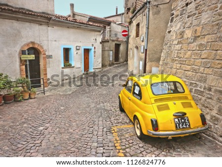 28.08.2015.Pietrapertosa, Basilicata Italy - vintage yellow car Fiat 500 on the old narrow street in small village in South Italy