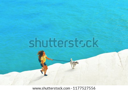 28.08.2018. Young woman in yellow dress running with dog on the white rocks in beach Scala Dei Turchi with turquoise blue mediterranean sea in background. Agrigento, Sicily Italy