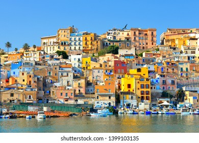 28.08.2018.Fishing boats with background of the colorful old houses with windows and blue sky in city of Sciacca overlooking its harbour. Province of Agrigento, Sicily.