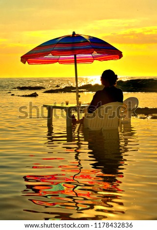 28.08.2018.woman sitting on chair immersed in the sea water, relax and drink coffee under umbrella with the background of a colorful warm summer sunset and beautiful water reflections, Agrigento Italy