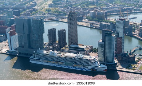 28-6-18, Rotterdam, Holland. Backlight aerial view of AIDA cruiseship at the passenger terminal at the WILHELMINAKADE, KOP VAN ZUID. High rise skyscrapers at the pier in river MAAS, Port of Rotterdam