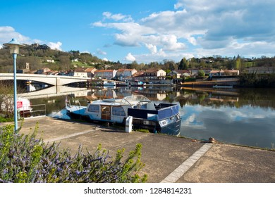 28th March 2017 -  Saint- Sylvestre-sur-Lot, France: Boats moored in spring morning sunshine on the placid River Lot at Saint- Sylvestre-sur-Lot, Lot-et-Garonne, France.