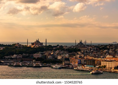 29 August 2019; Istanbul, Turkey; Distant, aerial view of the Hagia Sophia museum and Sultan Ahmed mosque with the Golden Horn and ferryboats in the foreground.