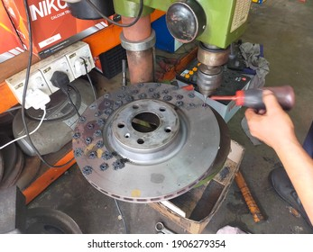 29 Jan. 2021 - KL, Malaysia : Selective focus of a mechanic making small holes in the disc brake. The bench drill or pillar drill in small version is used for drilling light weight pieces of material.