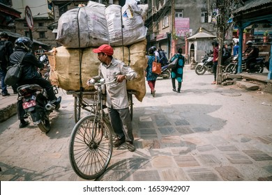 29th April 2019 Kathmandu Nepal : Nepali holding bicycle loading with big bags on the street of old town in Kathmandu the capital city of Nepal