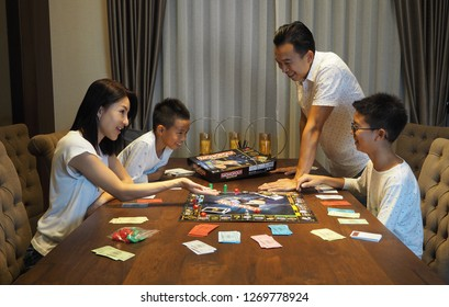 29th December 2018, Bangkok Thailand. Asian family playing Monopoly board game together at night. Father, mother, older son and younger son enjoying the game.