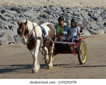 29th September 2018- A horse and carriage being driven on the sandy beach at Pendine, Carmarthenshire, Wales, UK.