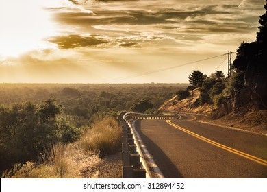 2-lane road during sunrise or sunset with view of valley in the background with a high dynamic sky