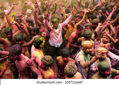 2nd March 2018, Guwahati, Assam, India. Coloured powder is thrown on men as they dance during Holi celebrations on street at Fancy Bazar, Guwahati.