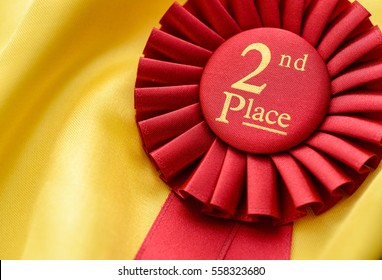 2nd place red winners rosette with pleated ribbon and gold text on a soft background of golden textile with copy space