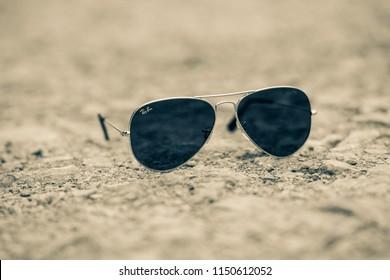 02b9bc11ae 2nd-Aug-2018 - Ashbourne - Derbyshire - Rayban aviator sunglasses on a  gravel