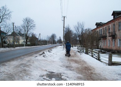 2th of December 2017 - Scene from Russian winter city with view to a woman with a stroller walking down a snowy desereted street, Ust Luga, Russia