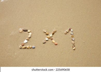 2x1 discount word writing with small stones on sand beach ground