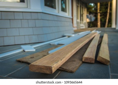 2x4 boards and lumber in pile on porch; ready for remodeling and home improvement.