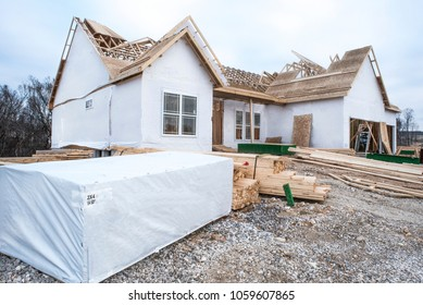 2x4's and lumber stacked in front of new home construction site in subdivision with partially built house wrapped in vapor barrier