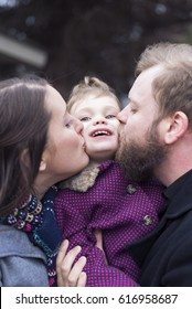 2-year-old girl in between parents kissing her on each cheek. Lovely family photo outdoors, authentic people.