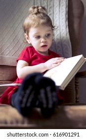 2-year-old girl holding and reading book, sitting on chair by window to left. Candid photo.