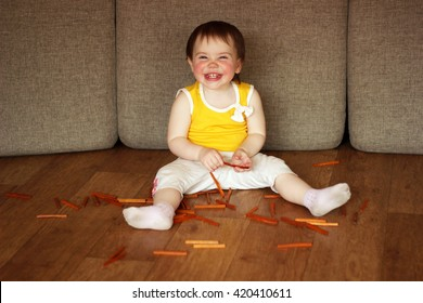 2-year-old girl playing with wooden sticks on the floor and laughs.