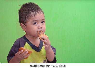 2years old baby(asian- malay race) eat pancake isolated green background