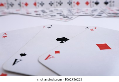 3 aces with other playing cards in the background