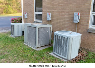 3 Air Conditioner Compressors outside commercial building with cutoff switches.