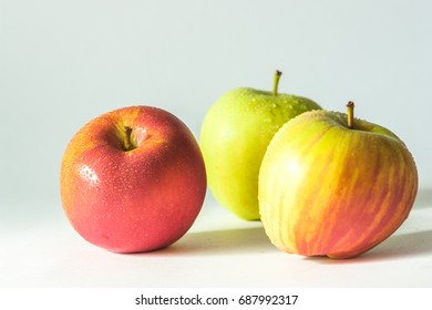 3 apples with water droplets on white background