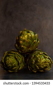 3 artichokes stacked on grey textured background