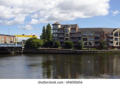 3 August 2017 Apartments on the bank of the River Lagan beside the Queen's Bridge in central Belfast with the iconic Harland and Wolff shipyard cranes overlooking them view across the