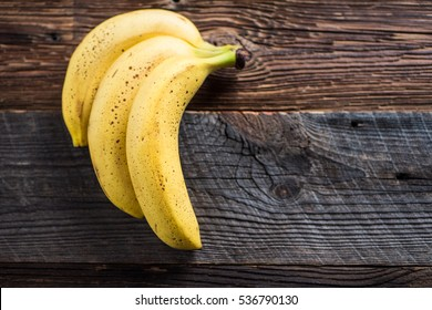 3 Bananas with dark spots on old wooden vintage table