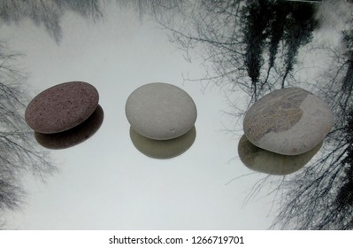 3 beach pebbles with reflections