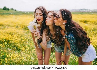 3 beautiful hippie girl in a field of yellow flowers