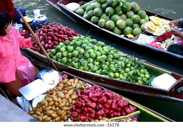3 boats carying vegetables and fruits at the Floating market in Thailand