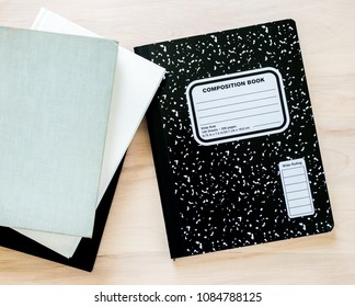 3 books next to a black and white composition notebook with blank cover for personalized title, all on a wooden desk