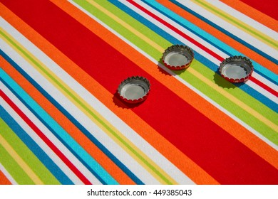 3 bottle caps laying outside on a bright summer colored table cloth.