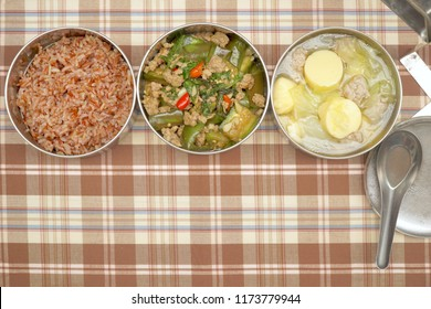 3 bowl of Antique stainless steel food carrier (Tiffin food container) and spoon. Set of food. Brown rice, Stir fried Eggplant, Soup with Tofu, Cabbage and Minced Pork. Free space for text. Simple.