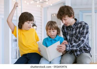3 boy read book outdoors on swing
