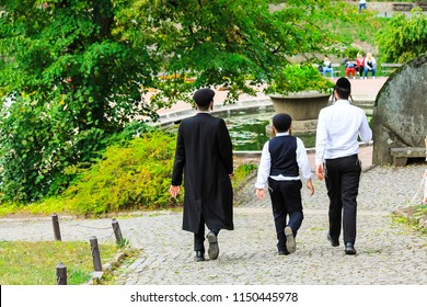 3 boys , a family of Hasidic Jews, in traditional clothes walk in the park in Uman, Ukraine, the time of the Jewish New Year, Rosh-ha-Shana