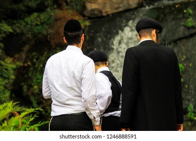 3 boys, a family of Hasidic Jews, in traditional clothes  stand in front of a waterfall in the park in Uman, Ukraine, the time of the Jewish New Year, religious orthodox Jew