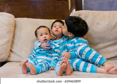 3 brothers play and hug each other on the sofa.