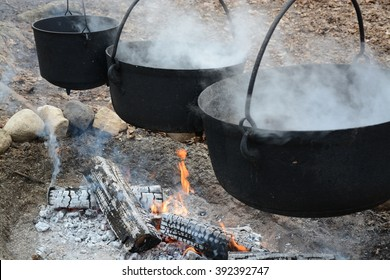 3 cauldrons of maple sap being boiled down over a fire