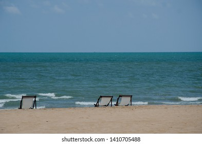 3 chairs on sand sea beach with no people