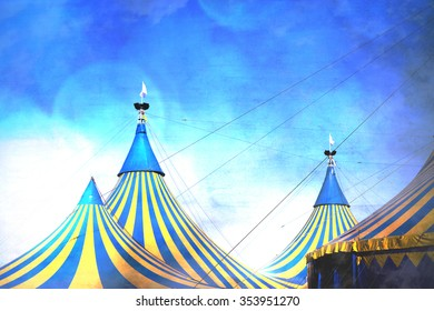 3 circus tent tops in yellow and blue stripes.  Dramatic blue sky with grunge bokeh effect creates dramatic scene