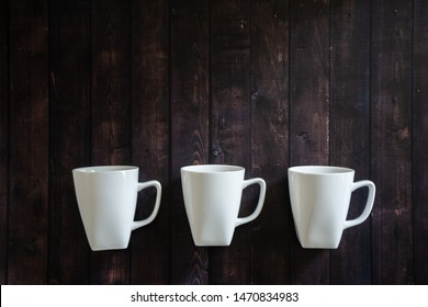 3 coffee mugs on a wooden table background - morning espresso java pick me up drink. Three cups of caffeine with blank empty room for text or copy space. Rustic look of a coffee house.
