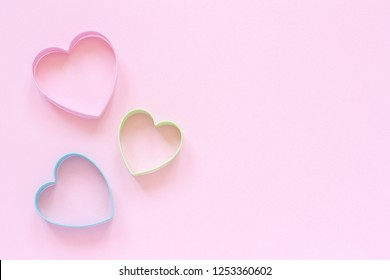 3 colored cutters cookies in heart shape on pastel pink background. Concept Valentine's card. Top view Copy space for text.