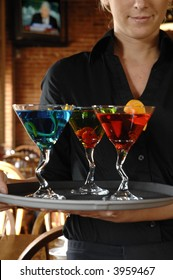 3 colorful drinks on a serving tray with waitress