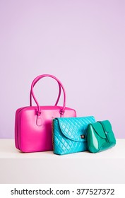 3 colorful leather bags and purses on the table. Isolated on light purple.